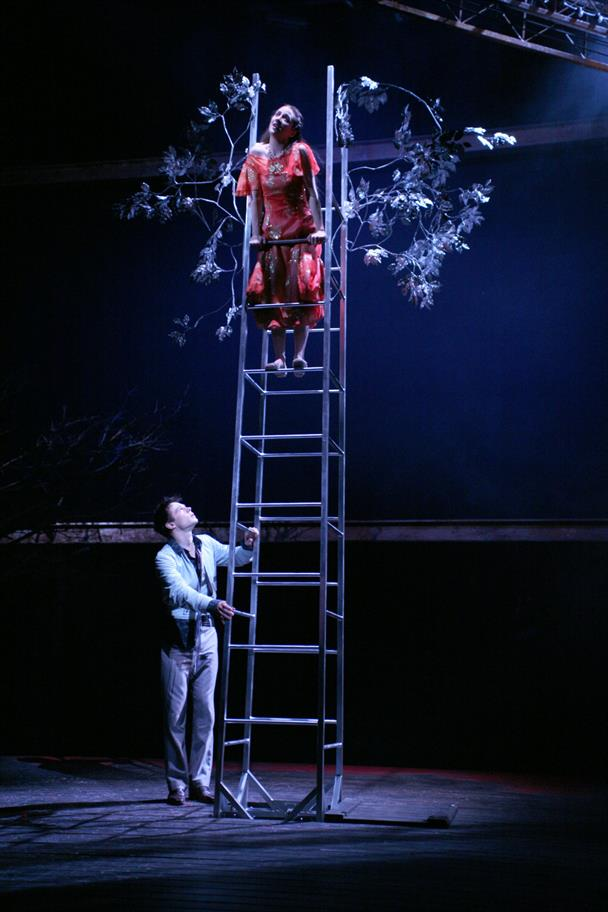 Juliet Stands At The Top Of A Ladder Supported By Romeo