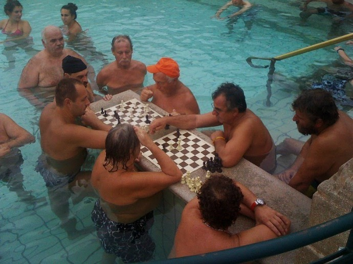 Some tourists are often seen relaxing while playing chess in a pool